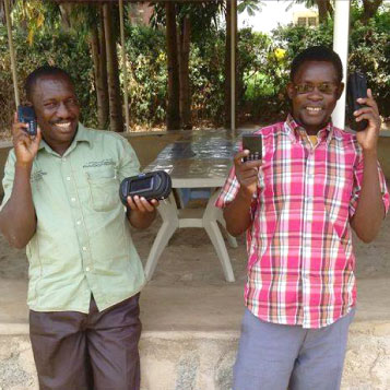 Two Men Listening To Audio Bibles And Holding Solar Case Speakers